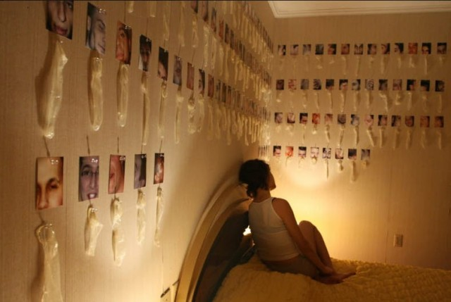 woman in bedroom with pictures attached to used condoms